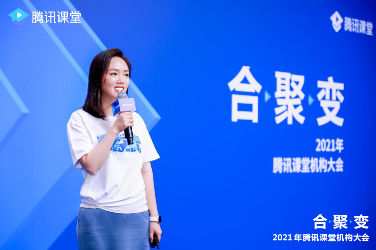A person holding a microphone and standing in front of a blue screen  Description automatically generated with medium confidence